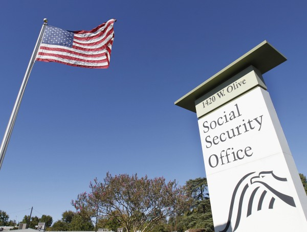 In this Oct. 25, 2012 file photo, an American flag flutters in the wind next to signage for a United States Social Security Administration office in Burbank, Calif.