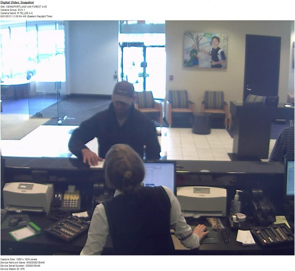 The robbery suspect demands money from a teller at the TD Bank branch at 449 Forest Ave. in Portland on Sept. 21, 2013.