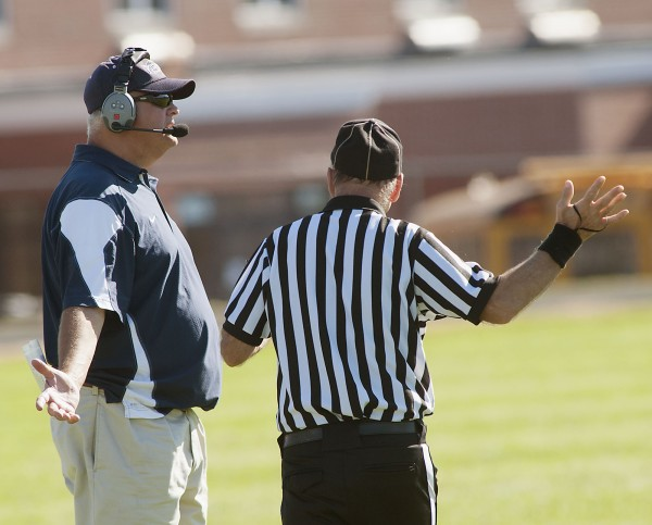 Portland High School football coach Jim Hartman questions a call in the second half of a football game against Bangor High School in Bangor, Maine, Saturday, Sept. 28, 2013.