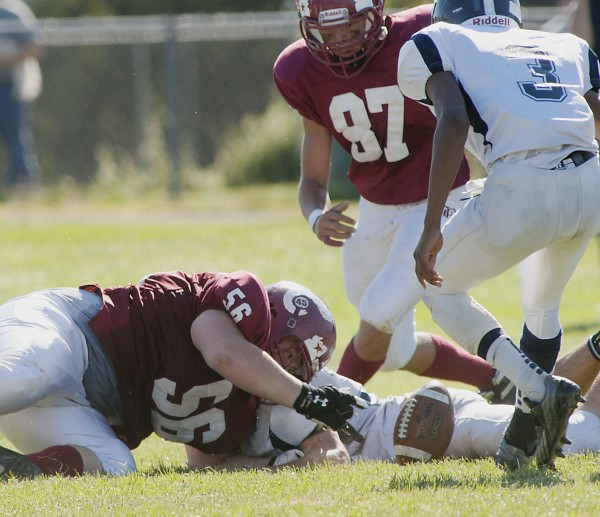 Bangor High School football player Tyler Flanagan (56) recovers a Portland fumble while teammate Jordan Ayer (87) and Portland player Jordan Talbot (3) focus on the prize in the second half of a football game in Bangor, Maine Saturday, Sept. 28, 2013.