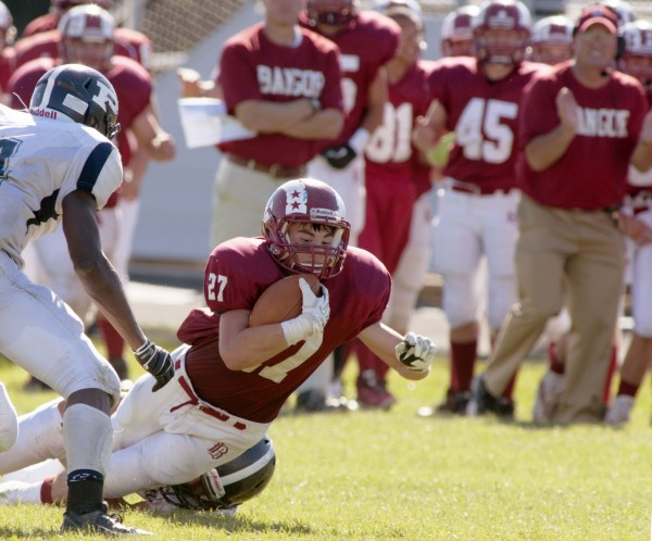 Bangor High School  football player Logan Lanham (27) is tackled after a carry in the second half of a game against Portland High School Saturday, Sept. 28, 2013, in Bangor, Maine.