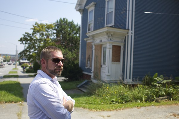 Code enforcement officer Jeremy Martin shows 308 Hammond St. in Bangor that has been boarded up to prevent vandalism and deter squatters.