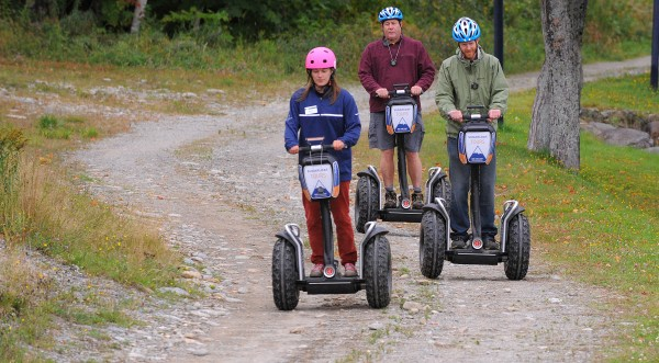 Meghan Price, (left) Segway guide and office manager, Sugarloaf Outpost Adventure Center and Ethan Austin, Sugarloaf Communications Manager demonstrate the Segway tour at Sugarloaf resort. At center is John Holyoke of the Bangor Daily News.
