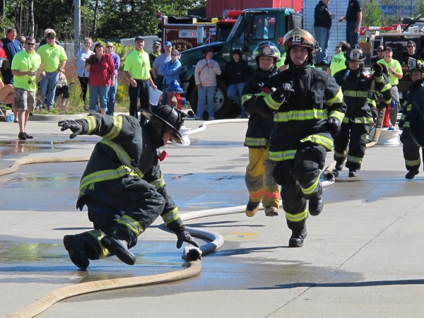 Members of the Southwest Harbor Fire Department run through a parking lot outside the former Lowe's building in Ellsworth on Sunday, Sept. 15, 2013, during a muster competition at the 50th annual Maine State Federation of Firefighters convention. The three-day event drew more than 1,000 people, including both firefighters and members of the public, according to organizers.