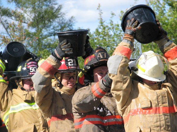 Members of the Fort Kent Fire Department participate in a 'bucket brigade' competition in Ellsworth on Sunday, Sept. 15, 2013, during the 50th annual Maine State Federation of Firefighters convention.