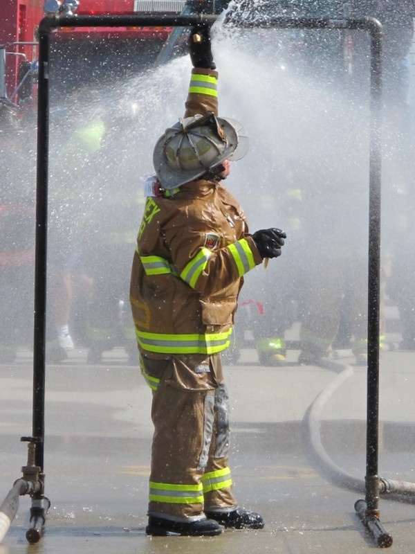 Bangor resident Hilari Simmons of the Blazin Babes muster team, from Glenburn and Hudson, tries to stem the flow of an activated sprinkler with wooden wedges on Sunday, Sept. 15, 2013, during the muster event at the 50th annual Maine State Federation of Firefighters convention in Ellsworth.