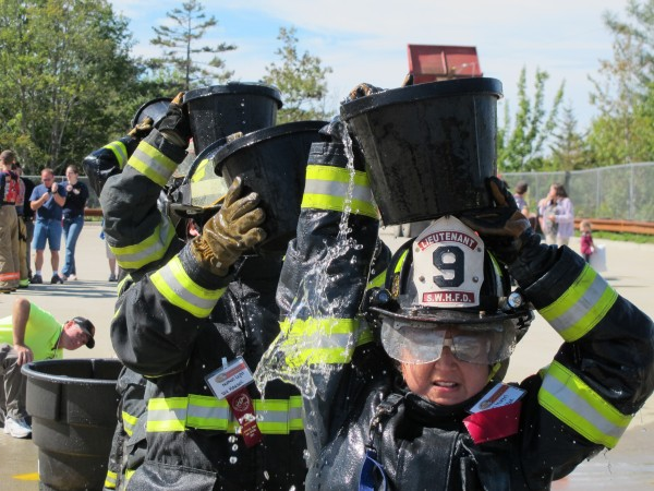 Jen Martel of the Southwest Harbor Fire Department balances a bucket of water on her head on Sunday, Sept. 15, 2013, during a competition at the muster event of the 50th annual Maine State Federation of Firefighters convention in Ellsworth.
