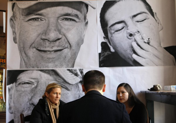 Large portraits of Portland's homeless are displayed on a wall behind customers discussing business over morning coffee at the Public Market House on Nov. 22.