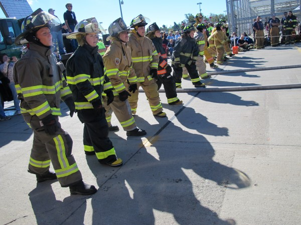 Members of the Blazin' Babes muster team from Glenburn and Hudson line up at a starting line on Sunday, Sept. 15, 2013, during the muster competition at the 50th annual Maine State Federation of Firefighters convention in Ellsworth.