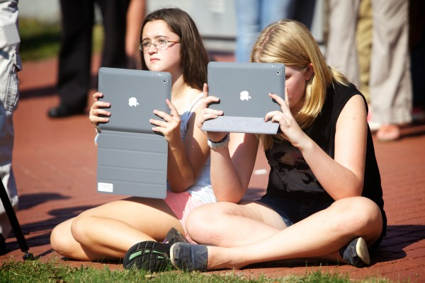 Freeport Middle School students Sophie Kaplan (left) and Grace Schnyder record events at a ceremony Wednesday morning marking the anniversary of Sept. 11, 2001, in Freeport.