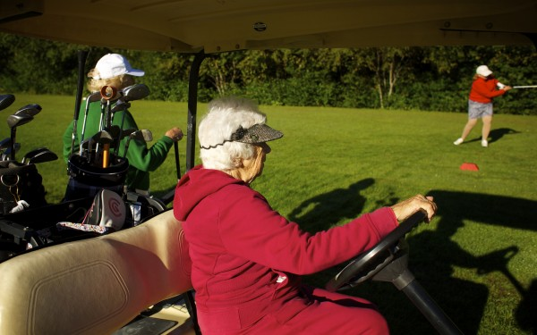 Hilda Wardwell (center) watches as a fellow golfer tees off last week at the Bangor Municipal Golf Course.