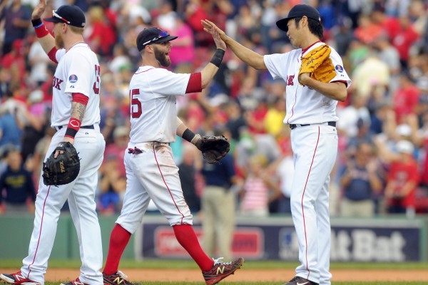 Boston Red Sox second baseman Dustin Pedroia (15) high fives relief pitcher Junichi Tazawa (right) after defeating the Chicago White Sox at Fenway Park in Boston Sunday.