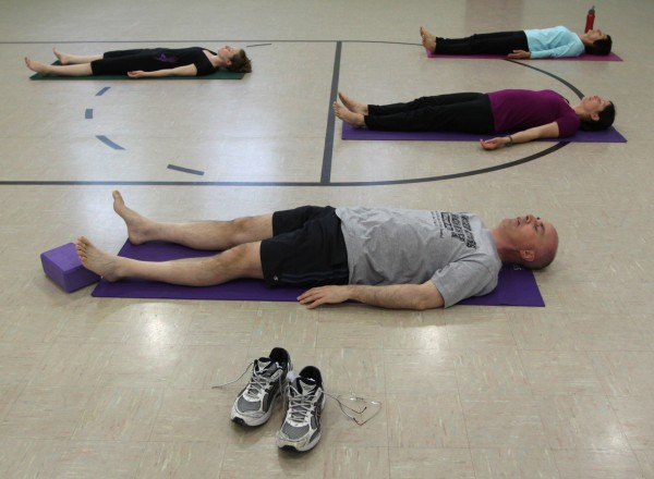 Marty Anderson, front, and others mediate at the start of a yoga class in Robbinsdale, Minnesota, in May 2011.