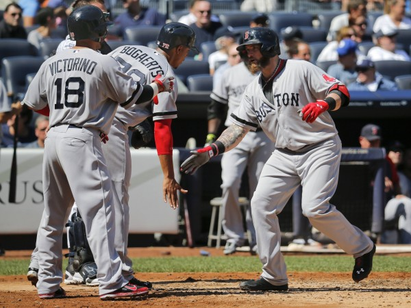 Boston's Jonny Gomes celebrates with runners Shane Victorino (18) and Xander Bogaerts after he hit a three-run home run against the New York Yankees in the third inning at Yankee Stadium in New York, September 7, 2013.
