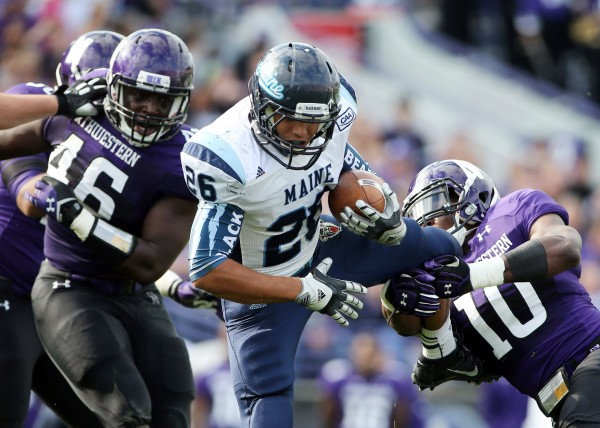 Maine Black Bears running back Nigel Jones (26) is tackled by Northwestern Wildcats safety Traveon Henry (10) and linebacker Damien Proby (46) during the second quarter Saturday at Ryan Field. Jones finished with 73 yards on 16 carries, including a 13-yard scoring run in the fourth quarter in Maine's 35-21 loss.