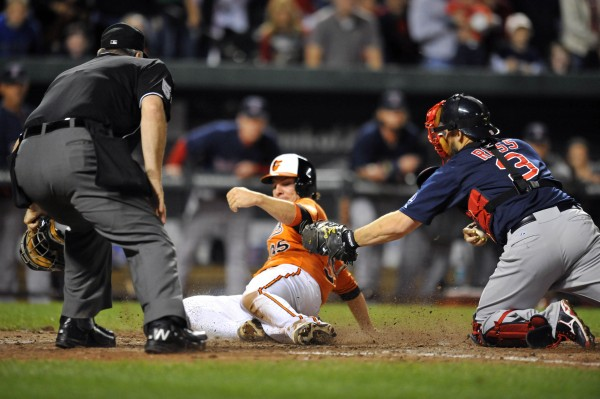 Baltimore's Danny Valencia scores the game-winning run on a two-run double by Steve Pearce in the eighth inning as Boston Red Sox catcher David Ross applies the late tag at Oriole Park at Camden Yards Saturday night. The Orioles defeated the Red Sox 6-5.