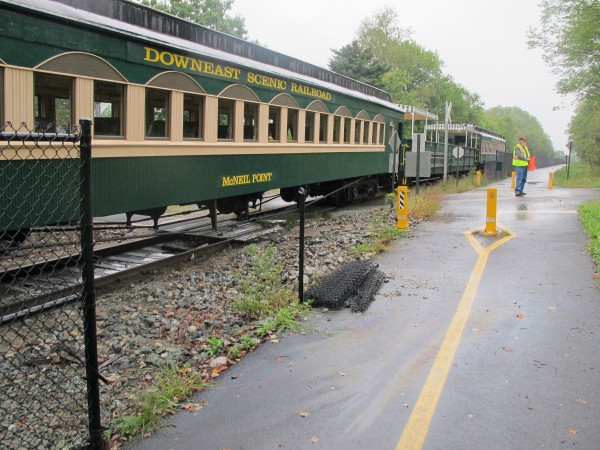 A Downeast Scenic Railroad train sits stopped at Davis Street in Ellsworth after it struck a car at the crossing on Monday, Sept. 2, 2013. The car was spun around by the impact and took out a section of chain link fence but the driver suffered only minor injuries, according to witnesses.