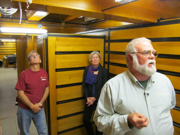 John Bishop, right, and Kathleen Grammar of the Friends of the Kotzschmar Organ join restorationist Phil Carpenter inside the massive instrument's windchest, which pressurizes with air and then, when played by an organist, releases that air through any of approximately 6,800 tuned pipes overhead.