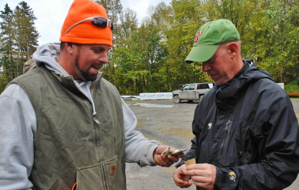 Chad Fenton, left, hands over the cash prize to hunting buddy Seamus McFlanagan after his fellow lobsterman correctly guessed the exact weight of the bull moose shot by Fenton Tuesday morning.