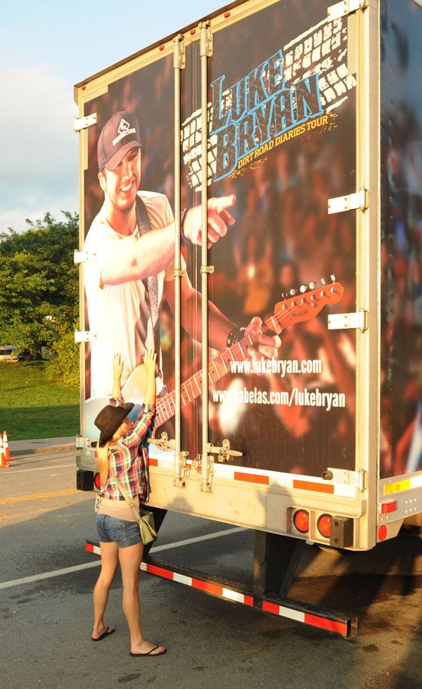 Alexa Coleman of Amherst, Nova Scotia, hugs one of  Luke Bryan's tour trucks outside of the Darling's Waterfront Pavilion along the Bangor Waterfront on Saturday prior to the start of the show.