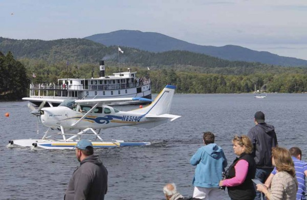 The steamship Katahdin heads north on Moosehead Lake while a Cessna seaplane glides southward during the International Seaplane Fly-In on Saturday.