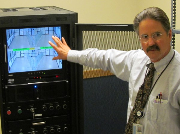 Cuyler Feagles, assistant facilities manager at the Portland International Jetport, gestures toward video screens that show a secured passageway leading arriving passengers away from the boarding area. If an individual moves in the opposite direction — from the unsecured area toward the secured concourse — the area will automatically be sealed shut and alarms will sound.