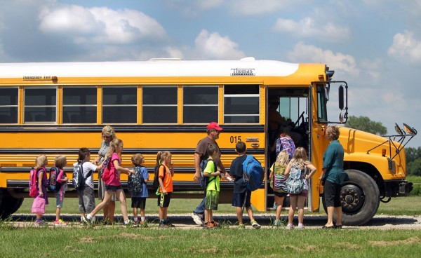 Students board a bus on the first day of school in Bates County, Mo., on Aug. 14, 2013.