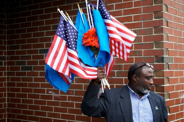Mohamud Barre, executive director of the Somali Culture and Development Association of Maine, holds a bouquet of Somali and American flags outside the Islamic Society of Portland Tuesday.