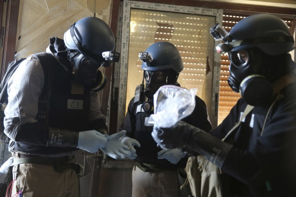 A U.N. chemical weapons expert, wearing a gas mask, holds a plastic bag containing samples from one of the sites of an alleged chemical weapons attack in the Ain Tarma neighbourhood of Damascus on Aug. 29.