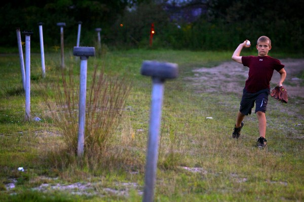 Christian Carrieri, 10, of Melrose, Mass., plays catch with his father before a double feature at Westbrook's Prides Corner Drive-In. It was Carrieri's first time at a drive-in.