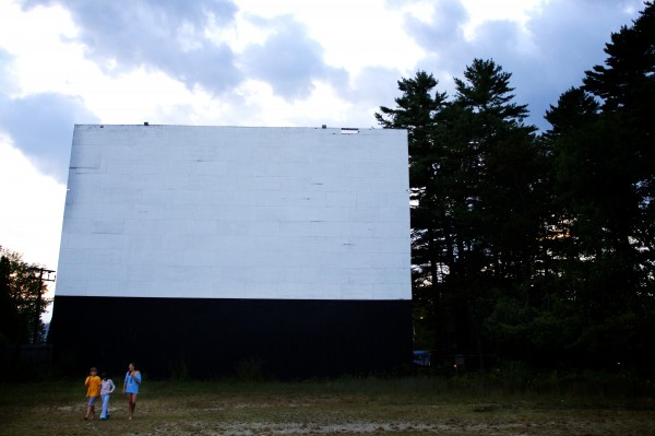 Kids stroll under the big screen at the Prides Corner Drive-In as night falls in Westbrook. Andrew Tevanian, whose father opened the drive-in in 1953, told the BDN in August, &quotIt's not just a drive-in, but a way of life.&quot