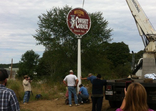 Larry Russell and other members of the &quotCherch of the Holy Cow&quot help erect a new sign marking &quotCowshit Corner&quot Saturday afternoon. The original sign was stolen earlier this summer.