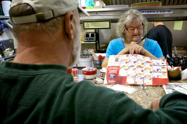 Waitress Angie Miller pitches her grandson's Boy Scout popcorn to patrons at Jen's Place in Brunswick Tuesday morning. The eatery, known for its eccentric clientele and staff, may soon get its own reality television show.