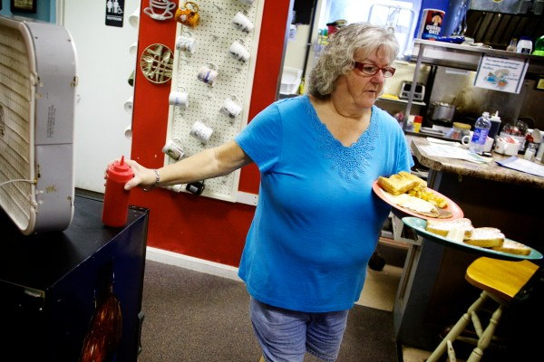 Angie Miller grabs the ketchup at Jen's Place in Brunswick Tuesday morning. The eatery, known for its eccentric clientele and staff, may soon get its own reality television show.