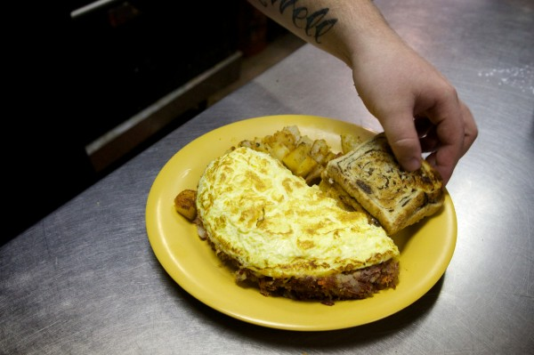 Cook Andrew Cogswell serves up a hash omelette at Jen's Place in Brunswick Tuesday. The eatery, known for its eccentric clientele and staff, may soon get its own reality television show.