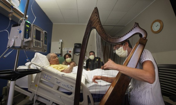 Annie Burgard, right, plays the harp and sings for Jack Davis, from left, his wife Irma and son Randy, in his room at Palmetto Health Richland in Columbia, S.C., Sept. 5, 2013. He is in pain from acute leukemia and Burgard uses her gift to help him relax and sleep.