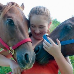 Meghan Murphy, 12, of Cape Elizabeth, poses with Dreamer and Murphy at Triple J Farm in Bowdoin on Wednesday. The two horses were saved last month from a kill pen in Washington state.