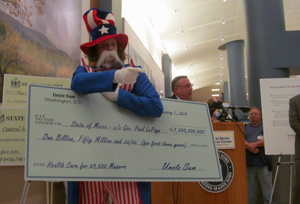 A protester from Maine People's Alliance holds a huge check representing the $1.05 billion federal funding available to Maine for Medicaid expansion. This spring, Gov. LePage vetoed a bipartisan bill to accept the money and expand publicly funded health insurance for roughly 70,000 Mainers.