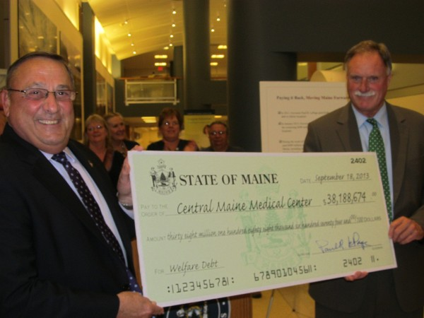 Gov. Paul LePage (left) hands over a check for more than $38 million to Peter Chalke, president and CEO of Central Maine Medical Center. The check represents the combined payment from Maine and the federal government for past Medicaid debt.