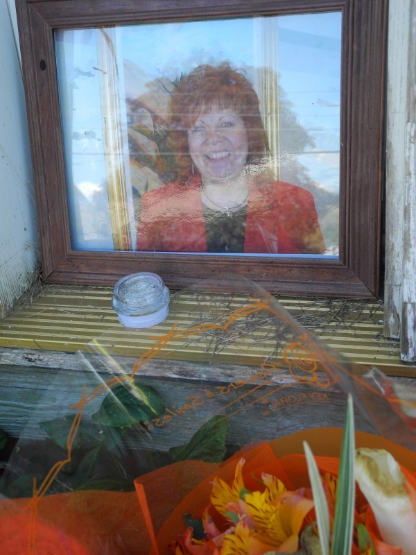 As part of a makeshift memorial, a photo of Lynn Arsenault was propped against the door of the house in which she was killed last week.