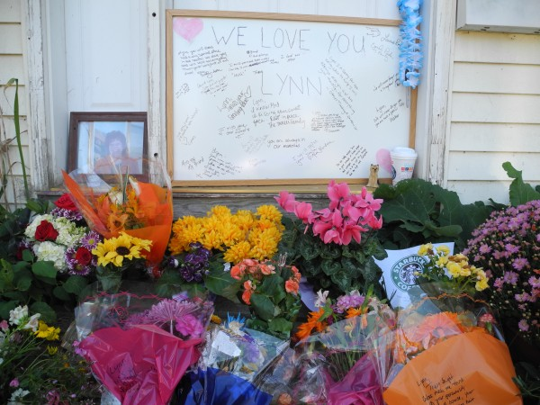 A memorial for Lynn Arsenault has sprung up at the front door of the house where she was killed last week.