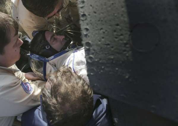 Russia's space agency ground personnel help US astronaut Chris Cassidy to get out of the Soyuz TMA-08M space capsule shortly after it landed some 146 km southeast of the town of Zhezkazgan in Kazakhstan, Sept. 11, 2013.