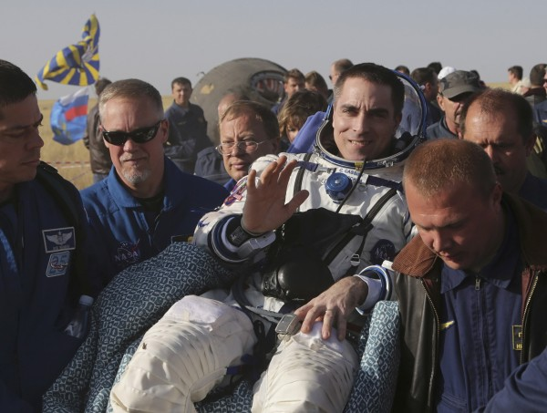 Russia's space agency ground personnel carry US astronaut Chris Cassidy (C) shortly after he landed in the Soyuz TMA-08M space capsule some 146 km southeast of the town of Zhezkazgan in Kazakhstan, Sept. 11, 2013.
