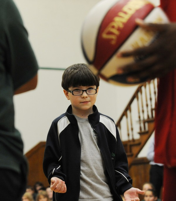All Saints Catholic School student Liam Hillary waits for the ball to be passed to him as Harlem Globetrotter Jet Williams delivers an anti-bullying message on Monday at the Bangor school.