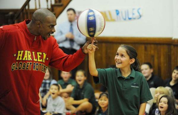 Harlem Globetrotter Jet Williams puts a spinning basketball on the finger of All Saints Catholic School student Casey Britt during an anti-bullying session conducted by Williams on Monday at the Bangor school.