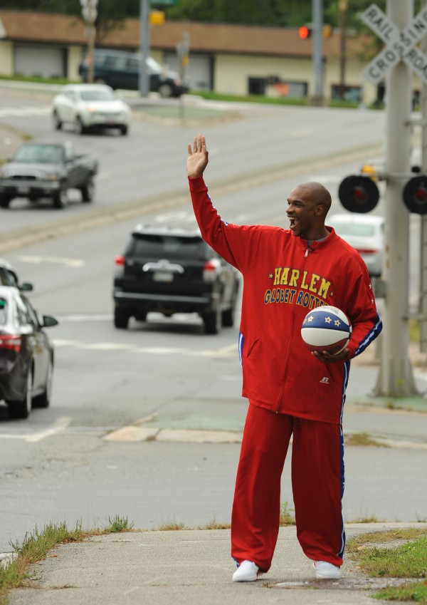 Harlem Globetrotter Jet Williams waves to passing motorists as they honk their horns during his ball dribbling and spinning publicity trek across the Penobscot Bridge on Monday.