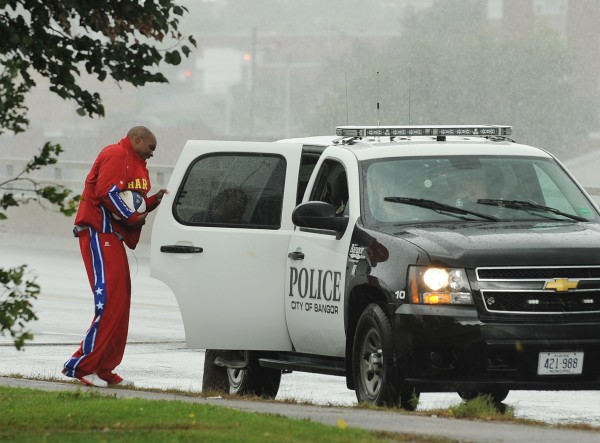 Harlem Globetrotter Jet Williams ducks into a Bangor Police vehicle as his basketball dribbling and spinning publicity trek gets cut short due to a downpour of rain on Monday along the Penobscot Bridge.