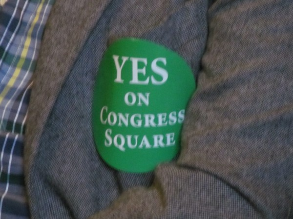 While protesters demonstrated against the proposed sale of a portion of Congress Square Park outside City Hall, supporters of the transaction, wearing green stickers like this one, lined up for chairs at the City Council meeting inside. The council was scheduled to discuss the sale at its Monday night meeting.