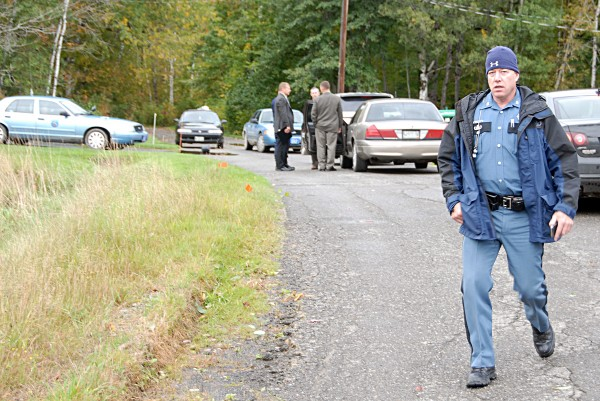 State police detectives, left, confer on Beaver Dam Point Road in Island Falls after the arrest of Matthew Davis, 32, of Houlton, on Monday, Sept. 23, 2013.