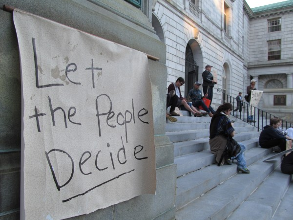 A sign posted by protesters Monday outside Portland City Hall urges city councilors to &quotlet the people decide&quot whether a portion of the publicly owned Congress Square park should be sold to private developers. A poll conducted of city residents earlier this month indicated that 63 percent of Portlanders want the decision to go to the polls as a public referendum.